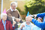 Senior man pouring champagne into glass on a birthday garden party - ZEF001030