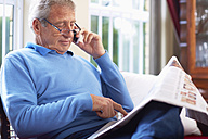 Senior man reading newspaper at home - ZEF001047
