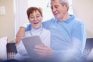 Happy senior couple using digital tablet at home - ZEF001057