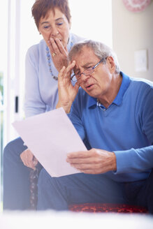 Shocked senior couple reading document at home - ZEF001062
