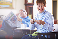 Senior woman knitting with husband in background reading newspaper - ZEF001064