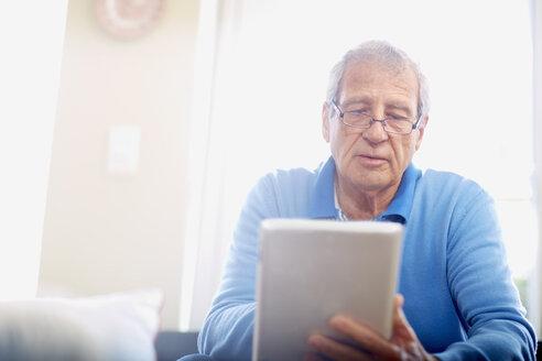 Senior man using digital tablet at home - ZEF001067