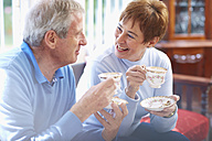 Happy senior couple drinking coffee at home - ZEF001069