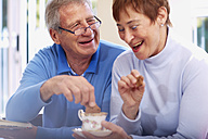 Happy senior couple drinking coffee at home - ZEF001071
