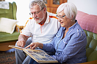 Senior couple at home looking at photo album - ZEF001089