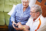Senior couple with smart phone at home - ZEF001094