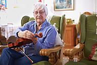 Senior woman at home tuning violin - ZEF001104