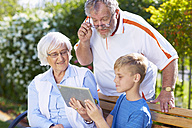 Grandson and grandparents using digital tablet in park - ZEF001117