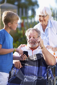 Grandmother and grandson explaining cell phone to grandfather in wheelchair - ZEF001140
