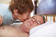 Senior woman kissing sick husband in bed - ZEF001152