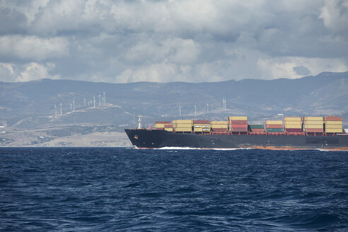 Spain, Andalusia, Tarifa, cargo ship on the ocean with coast in background - KB000181
