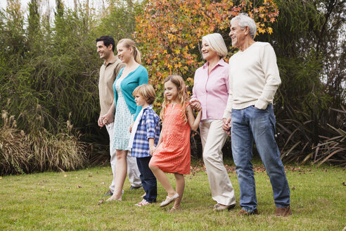 Extended family walking hand in hand in garden - WESTF020090