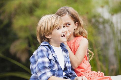 Girl whispering into boy's ear - WESTF020099
