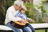 Grandfather and grandson with guitar outdoors - WESTF020102