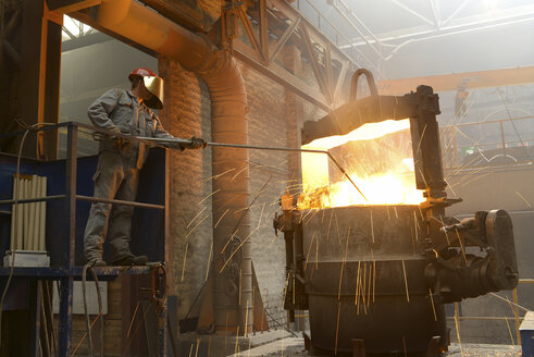 Worker checking temperature of material in a foundry - SCH000431