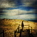 France, Contis-Plage, Silhouette of a man on wooden boardwalk - DWI000223