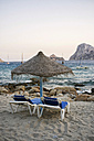 Spain, Balearic Islands, Ibiza, Cala Es Vedra, sunbeds with sunshade in the evening light - TKF000398