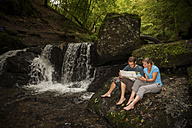Germany, Rhineland-Palatinate, Moselsteig, Ehrbachklamm, couple reading map at waterfall - PAF000997