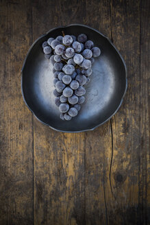 Bowl of deep frozen blue grapes on wood - LVF001946