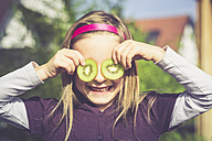 Laughing girl covering eyes with slices of kiwi - SARF000876