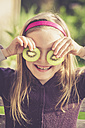 Smiling girl covering eyes with slices of kiwi - SARF000877