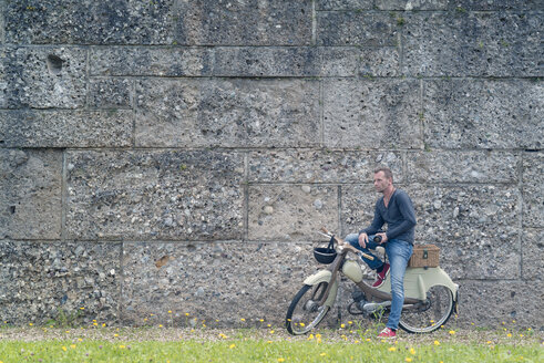 Photographer standing in front of a wall with his motor scooter - MW000075