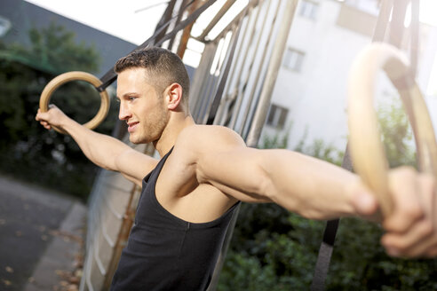 Muscly young man training on gymnastic rings - MAD000041