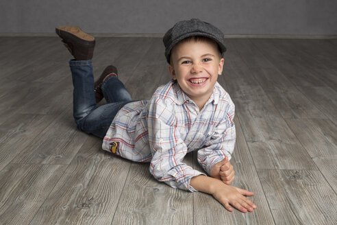 Portrait of smiling boy lying on the floor - SHKF000007