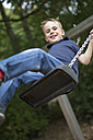 Portrait of smiling boy sitting on a swing - SHKF000003
