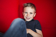 Portrait of smiling boy sitting on a red couch - SHKF000004