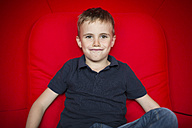 Portrait of boy sitting on a red couch pouting mouth - SHKF000005