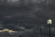 Football net in front of flood light and dark clouded sky - BSCF000441