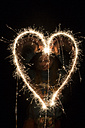 Teenage girl painting heart with sparkler at night - SARF000882
