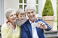 Germany, Hesse, Frankfurt, Senior couple taking selfie with granddaughter - RORF000053