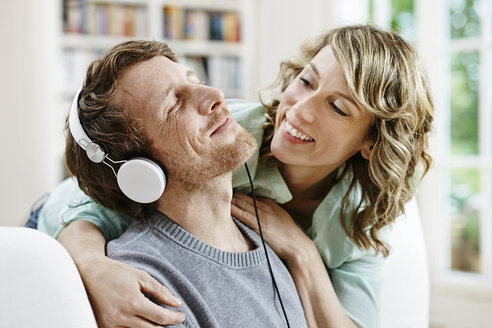 Germany, Hesse, Frankfurt, Adult couple at home listening to music - RORF000087