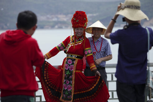 China, Erhai lake, tourists taking pictures of woman in traditional costume - DSG000223