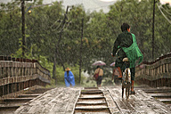 Myanmar, people on footbridge in monsoon rainfall - DSG000349
