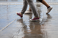 Slovenia, Koper, two people crossing Carpaccio Square at rainy weather - WI001119