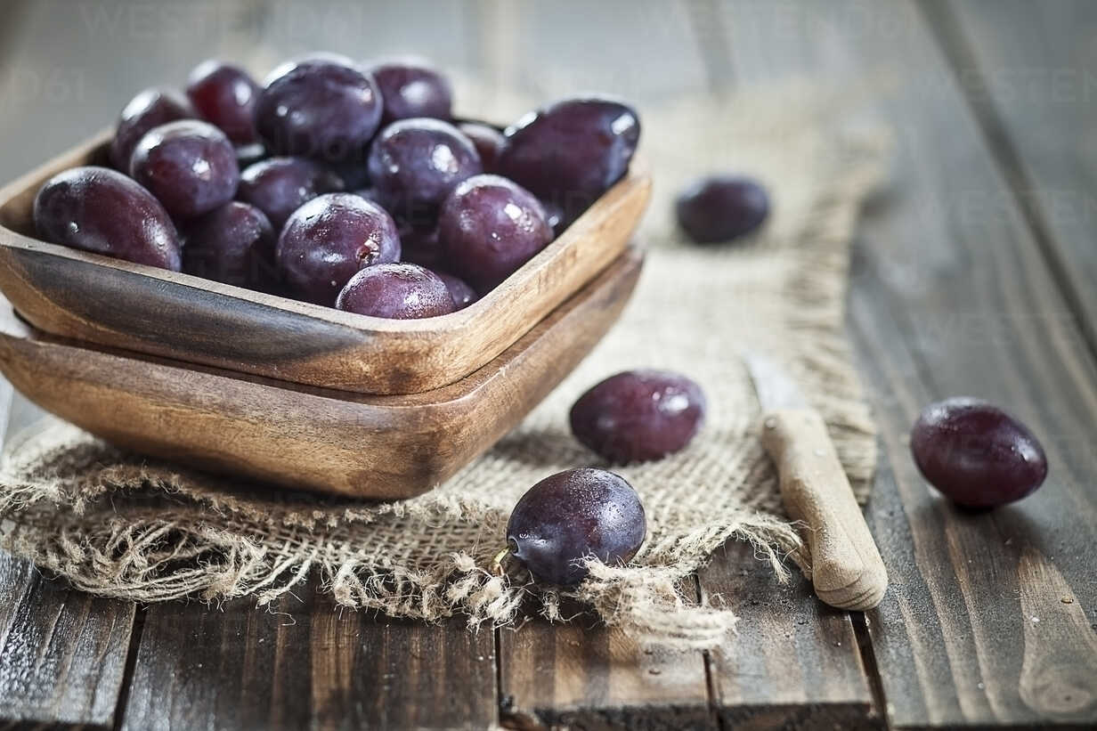 Wooden bowl of plums on jute and wood - SBDF001307 - Susan Brooks-Dammann/Westend61