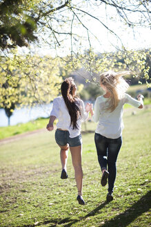Two female friends running together in a park - ZEF001222