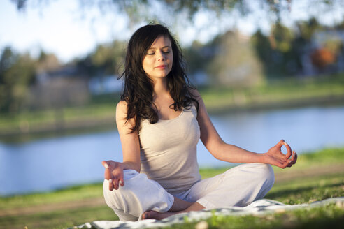 Young woman doing yoga exercise in a park - ZEF001223