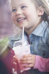 Portrait of smiling little girl with milkshake cup in coffee shop - ZEF001252