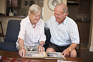 Senior couple with photo album - ZEF001311