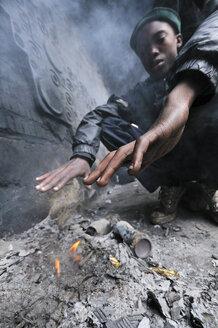 South Africa, Johannesburg, Hillbrow, street kid warming at fire - FLK000493