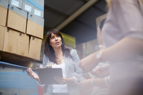 Woman with clipboard in warehouse talking to women - ZEF001467