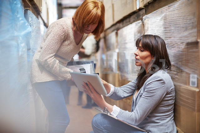 Woman with digital tablet in warehouse talking to woman - ZEF001437