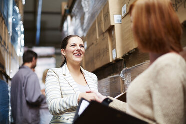 Two women shaking hands in warehouse - ZEF001443