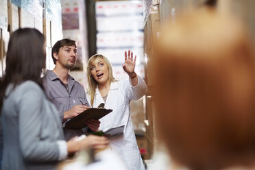Woman in warehouse talking to worker with clipboard - ZEF001444