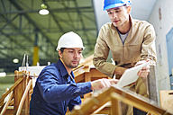 Construction worker and foreman discussing roof beams - ZEF001848