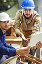 Construction worker and foreman discussing roof beams - ZEF001850